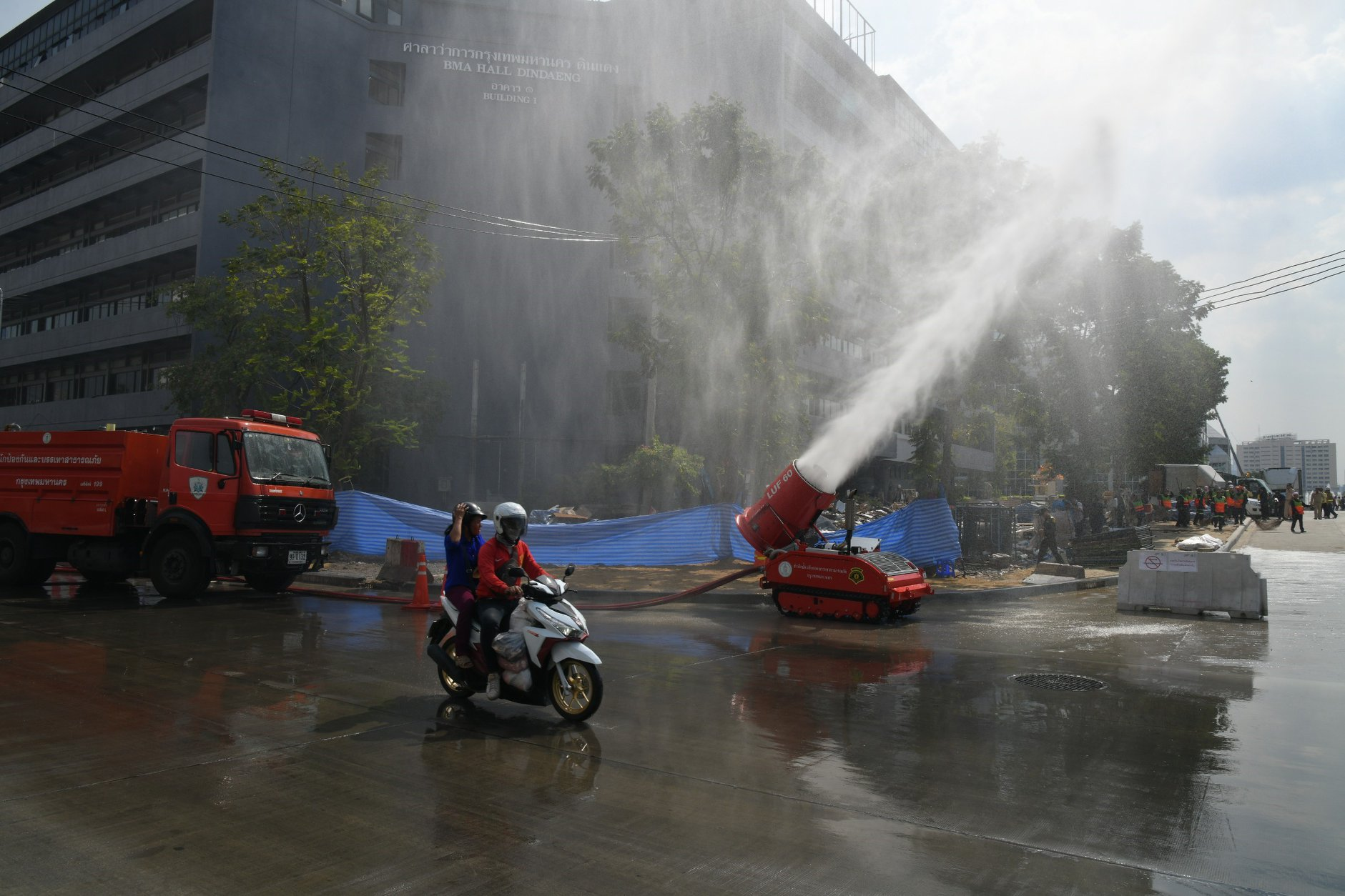 "City Hall workers spray water today in front of the Din Daeng police station in an attempt to reduce smog in the air. Bangkok's air quality was at ""moderate"" level Monday afternoon as officials warned pollution still exceeds acceptable standards in several areas, including Din Daeng, Thonburi and Bang Kapi."